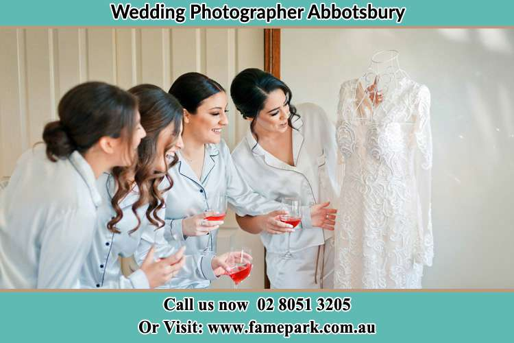 Photo of the Bride and the bridesmaids checking the wedding gown Abbotsbury NSW 2176