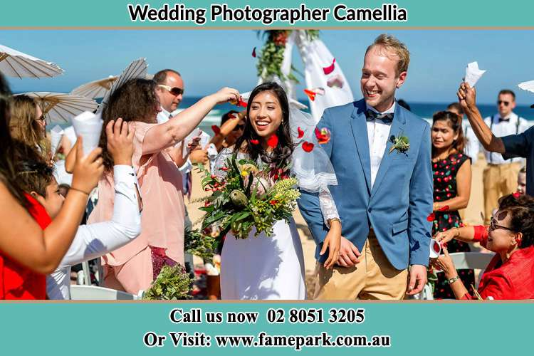 Photo of the Bride and the Groom showering flower petals by the visitors Camellia NSW 2142
