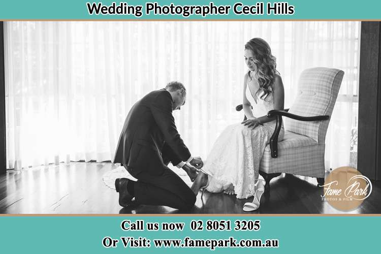 The Bride is being helped by the Groom trying to put on her shoes Cecil Hills NSW 2171