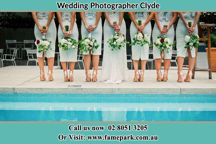 Behind photo of the Bride and the bridesmaids holding flowers near the pool Clyde NSW 2142