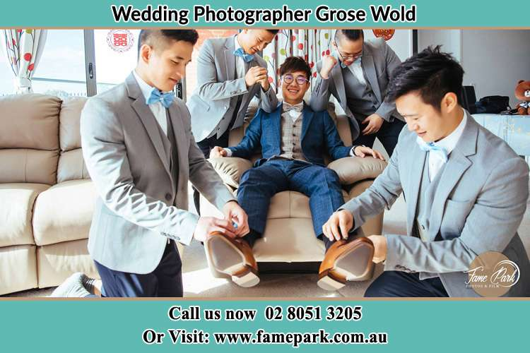 Photo of the Groom helping by the groomsmen getting ready Grose Wold NSW 2753