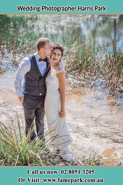 Photo of the Groom kiss the Bride near the lake Harris Park NSW 2150