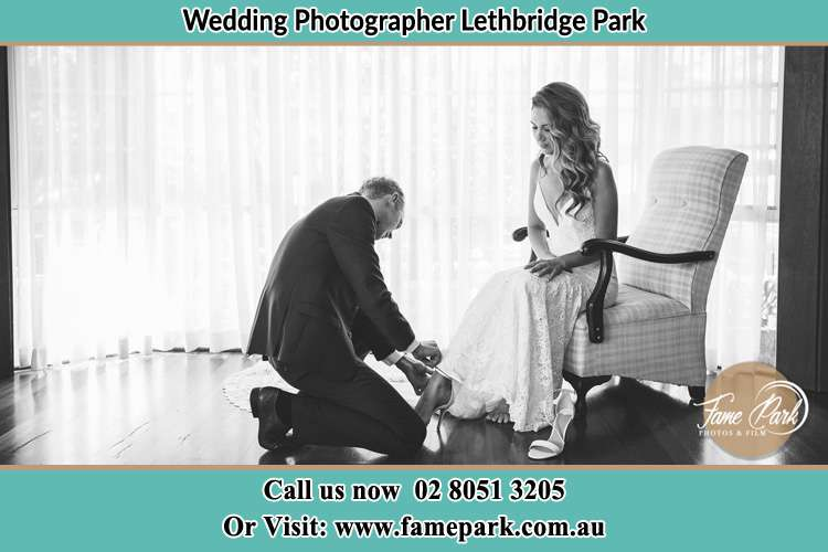 The Bride is being helped by the Groom trying to put on her shoes Lethbridge Park NSW 2770