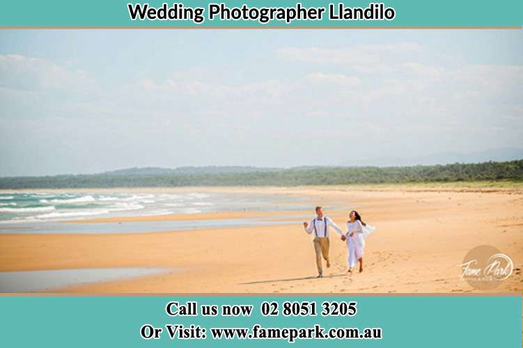 Photo of the Groom and the Bride walking at the sea shore Llandilo NSW 2747