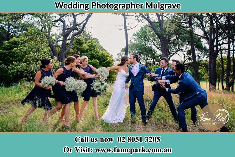 Photo of the Bride and the Groom kissing while teasing by the entourage Mulgrave NSW 2756