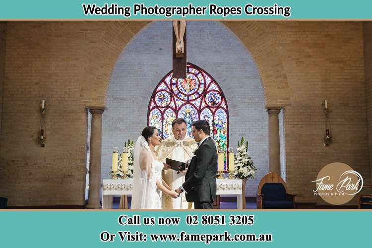 Photo of the Bride and the Groom with the Priest at the altar Ropes Crossing NSW 2760