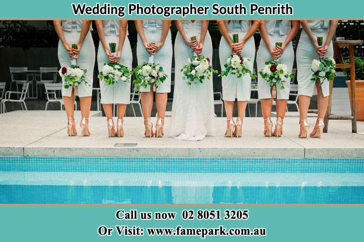 Behind photo of the Bride and the bridesmaids holding flowers near the pool South Penrith NSW 2750
