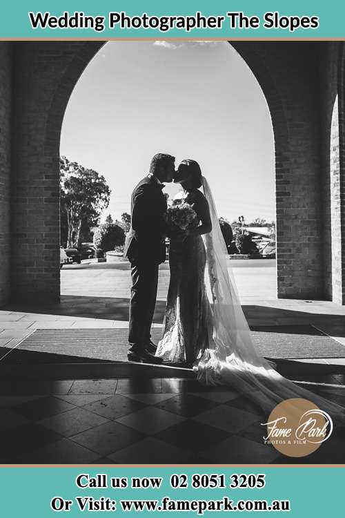 Photo of the Groom and the Bride kissing at the front of the church The Slopes NSW 2754