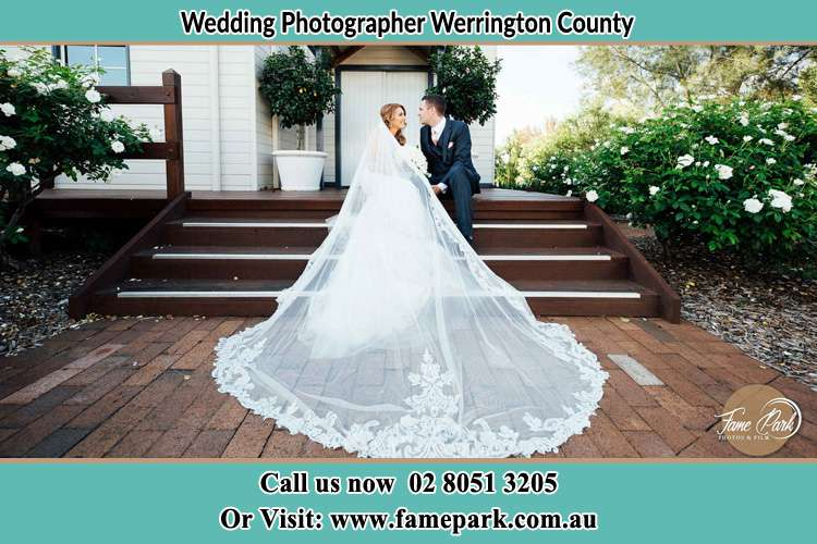 Photo of the Bride and the Groom looking each other while sitting at the staircase Werrington County NSW 2747