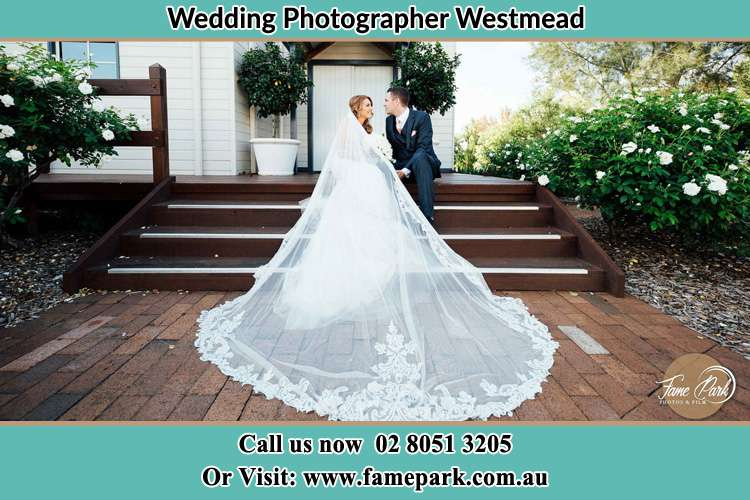 Photo of the Bride and the Groom looking each other while sitting at the staircase Westmead NSW 2145