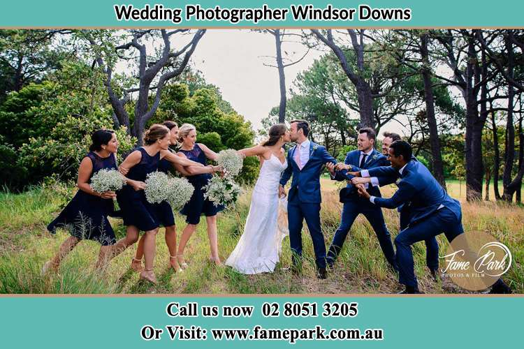Photo of the Bride and the Groom kissing while teasing by the entourage Windsor Downs NSW 2756